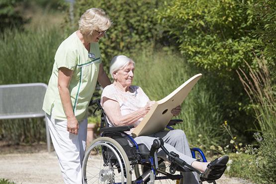 Pflegekraft und Stiftsbewohnerin im Park des KWA Albstifts Aalen
