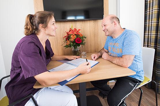 KWA Klinik Stift Rottal: Besprechung einer Pflegekraft mit einem Reha-Patienten