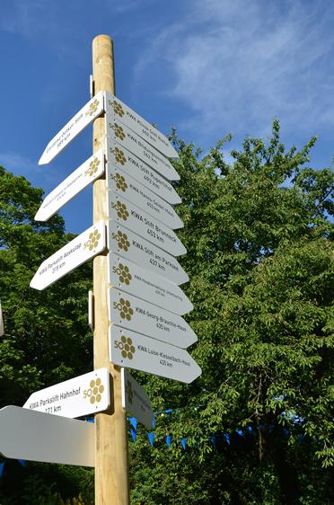 Ein Schilderbaum zum KWA Jubiläum im KWA Parkstift St. Ulrich in Bad Krozingen - mit Wegweisern zu allen KWA Standorten