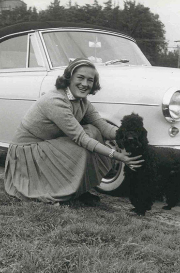 Elga Thouret mit Pudel vor ihrem Sportwagen