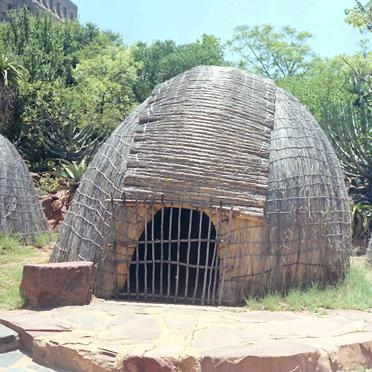 Zulu-Hütten (1988), die kunstvoll gepflochtenen Rundhütten sind kreisförmig angeordnet