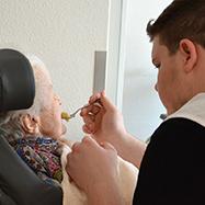 Der Bundesfreiwillige gibt einer Seniorin zu essen