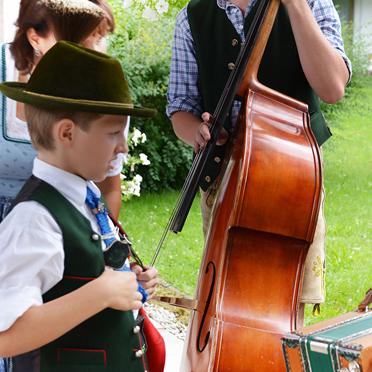 """Ein junger Hirschbergler interessiert sich für die Steirische Harmonika von Marinus Hampel, einem Mitglied der """"Haustischmusi Rottach"""""""