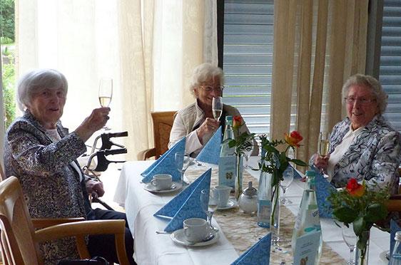Hier stoßen drei Stiftsbewohnerinnen auf 50 Jahre KWA an