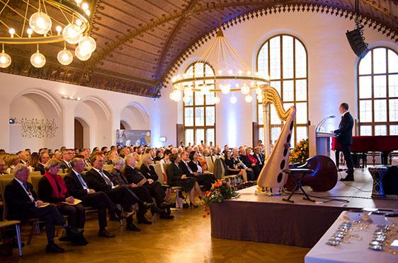 Der KWA Vorstand kündigt das Grußwort der Bayerischen Landesregierung an: vertreten durch Staatsministerin Emilia Müller.