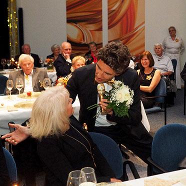 """50-Jahre-KWA-Feier im KWA Albstift Aalen: Stiftsdirektor Manfred Zwick verschenkt als """"Roy Black"""" weiße Rosen an einige Damen ..."""