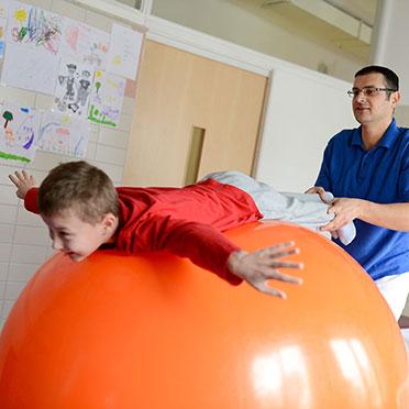 KWA Klinik Stift Rottal in Bad Griesbach, Neuroaktive Reflextherapie, hier mit Therapeut Yaroslav Prannyk: Auf dem Gymnastikball wird die Rückenmuskulatur gekräftigt und Rumpfstabilität gefördert.