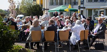 Bewohner und Gäste vor dem Bottroper KWA Wohnstift - mit Blick auf den Maibaum, der vom Kran aufgestellt wird