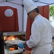 """Vor dem Eingang ist eine Freiluft-Bäckerei aufgebaut: Der Leiter des KWA Küchenbereichs Georg Tragenkranz legt ein atemberaubendes Tempo vor bei der """"Produktion"""" von Flammkuchen."""